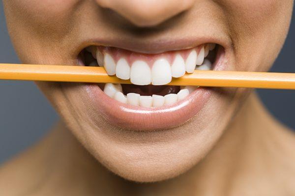 Карандаш между зубами