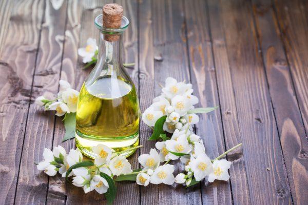 Бутылочка масла жасмина и цветы жасмина