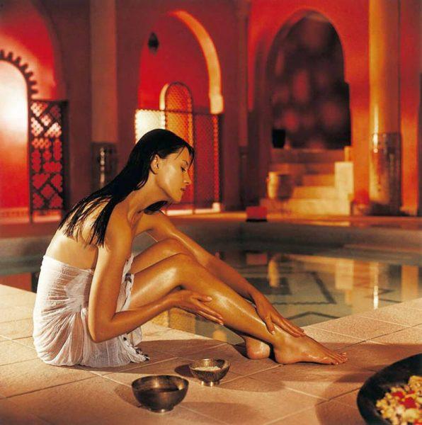 Девушка на краю бассейна делает массаж маслом