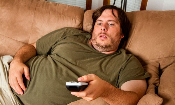 Мужчина лежит на диване и смотрит телевизор