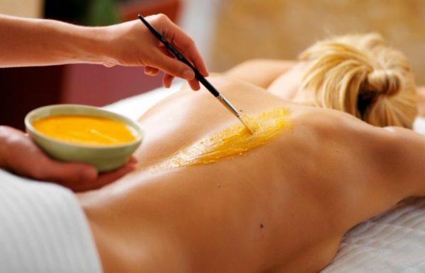 Нанесение загустевшего мёда на кожу девушки с помощью кисти
