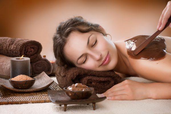 Нанесение шоколадного обёртывания на спину девушки