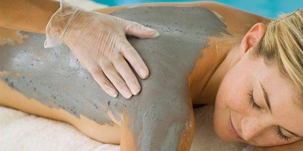 Нанесение состава для обёртывания на спину и руки девушки