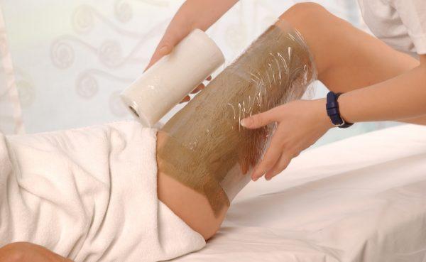 Оборачивание ноги девушки пищевой плёнкой