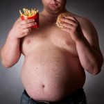 Мужчина держит в руках бургер и картофель фри
