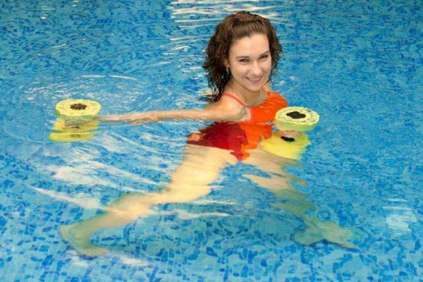 Женщина двигает гантели в воде по часовой стрелке