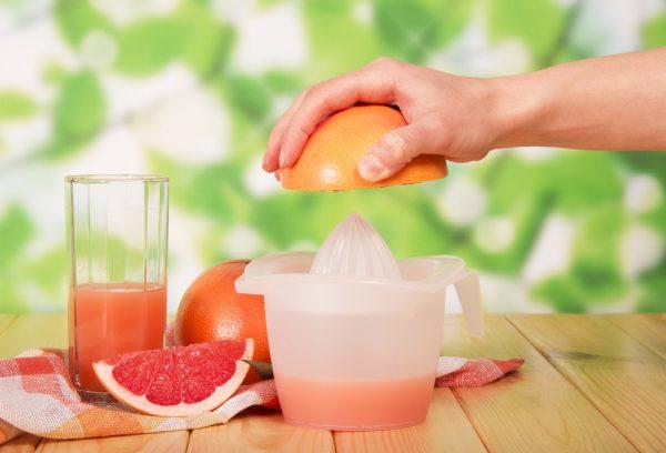 Сок грейпфрута в прозрачном стакане и плоды