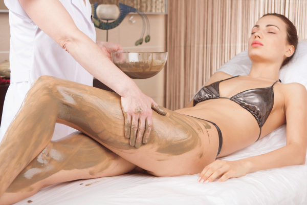 Специалист наносит антицеллюлитный состав на ноги девушки