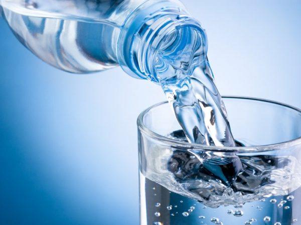 Воду из бутылки наливают в стакан