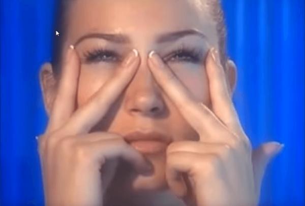 девушка прищуривает глаза и фиксирует кожу глаз