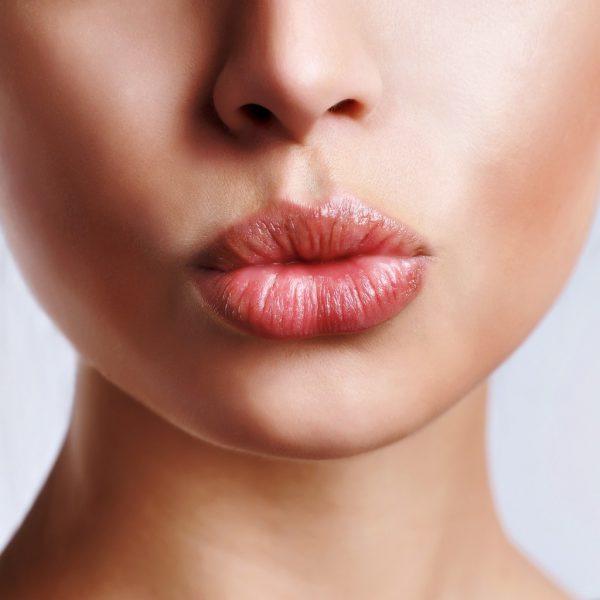 лицо девушки с губами. сложенными в трубочку