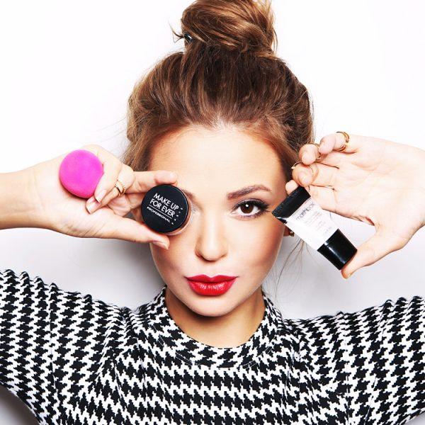 Девушка держит в руках ёмкости с декоративной косметикой