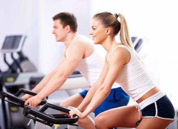 Девушка и парень занимаются на велотренажёрах