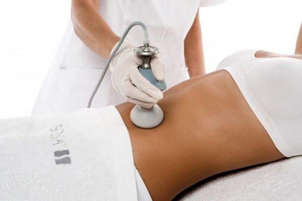 косметолог проводит по телу аппаратом для вакуумного массажа