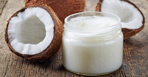 Кокосовое масло в прозрачной ёмкости и плоды в разрезе