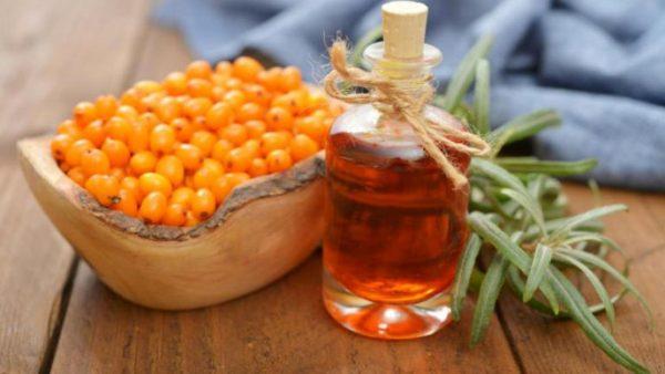 Облепиховое масло в прозрачном флаконе и ягоды