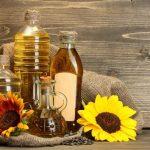 Подсолнечное масло в прозрачных ёмкостях и цветы