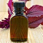 Амарантовое масло в тёмном флаконе и растение