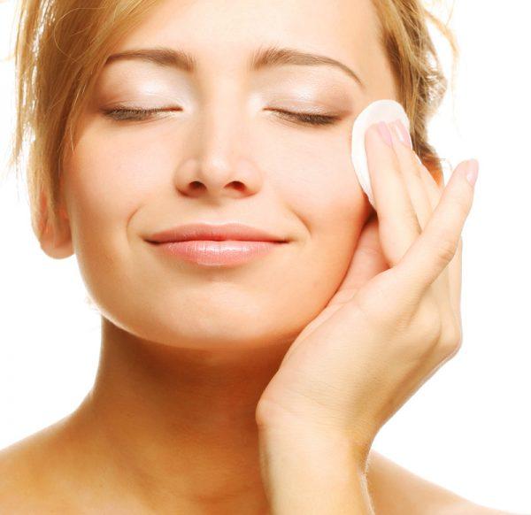 Девушка проводит по лицу ватным диском, чтобы снять макияж