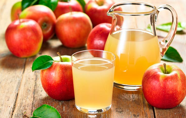 Яблочный сок в прозрачных ёмкостях и фрукты