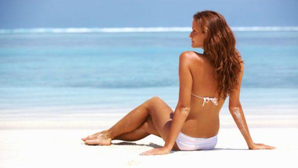 Женщина загорает на пляже