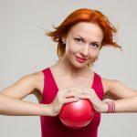 Девушка сжимает мяч ладонями, напрягая мышцы груди
