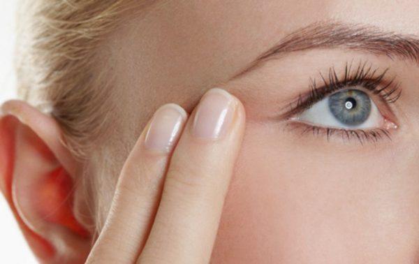 Два пальца на лице девушки и глаз