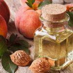 Масло персиковых косточек в прозрачном флаконе и плоды