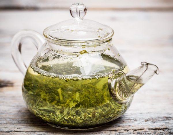 Заваренный зелёный чай в прозрачной ёмкости