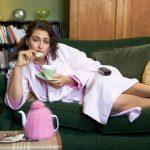 Девушка лежит на диване и ест