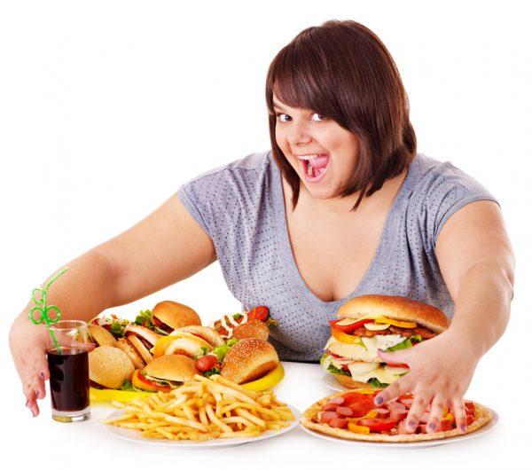 Полная женщина радуется изобилию вредных продуктов