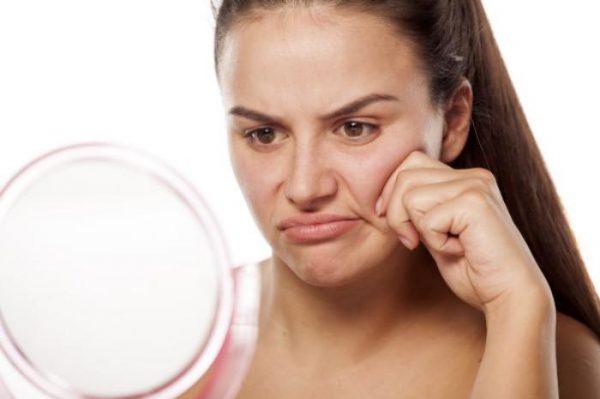 Женщина недовольна отражением своего лица в зеркале