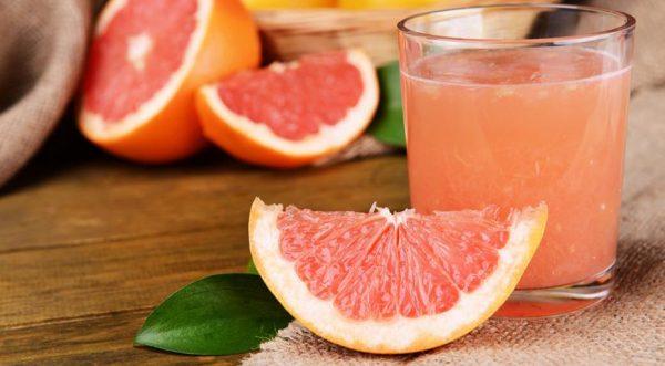 Сок грейпфрута в прозрачном стакане и фрукты