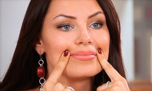 Женщина держит указательные пальцы на уголках рта