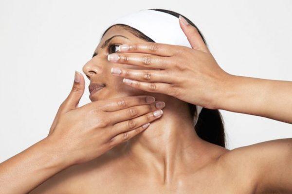 Женщина повернула голову влево, одной рукой держит кожу, а другой массажирует лицо