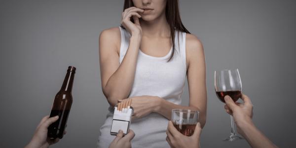 Девушке предлагают бутылку, сигареты и спиртные напитки, налитые в стакан и фужер
