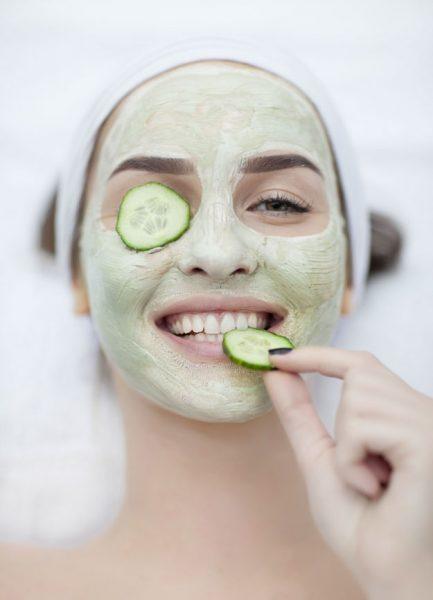 Женщина с огуречной маской и ломтиками огурца на лице