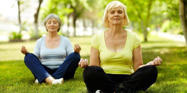 Женщины в возрасте медитируют на лужайке