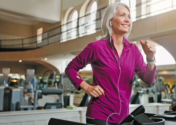 Седовласая женщина на беговой дорожке в спортзале