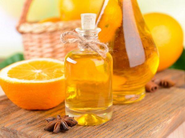 Эфир апельсина в прозрачных флаконах и фрукты
